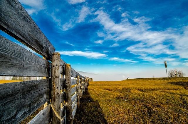 Valla y un campo con un cielo azul.
