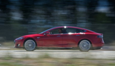 Tesla Model S rojo en carretera de perfil