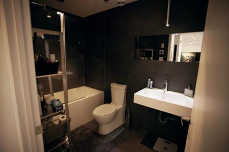 Un baño oscuro para el apartamento de 56 metros