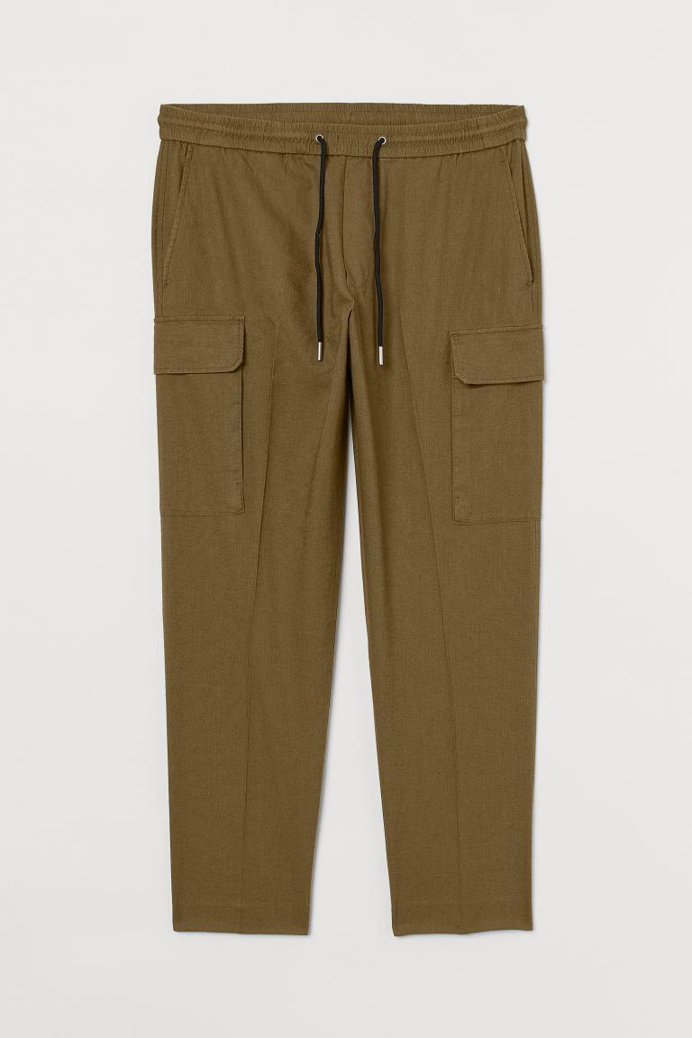 Pantalón cargo en mezcla de lino y algodón con cierre decorativo y cintura elástica con cordón de ajuste. Bolsillos al bies, bolsillos traseros ribeteados con solapa y bolsillos en las perneras con solapa.