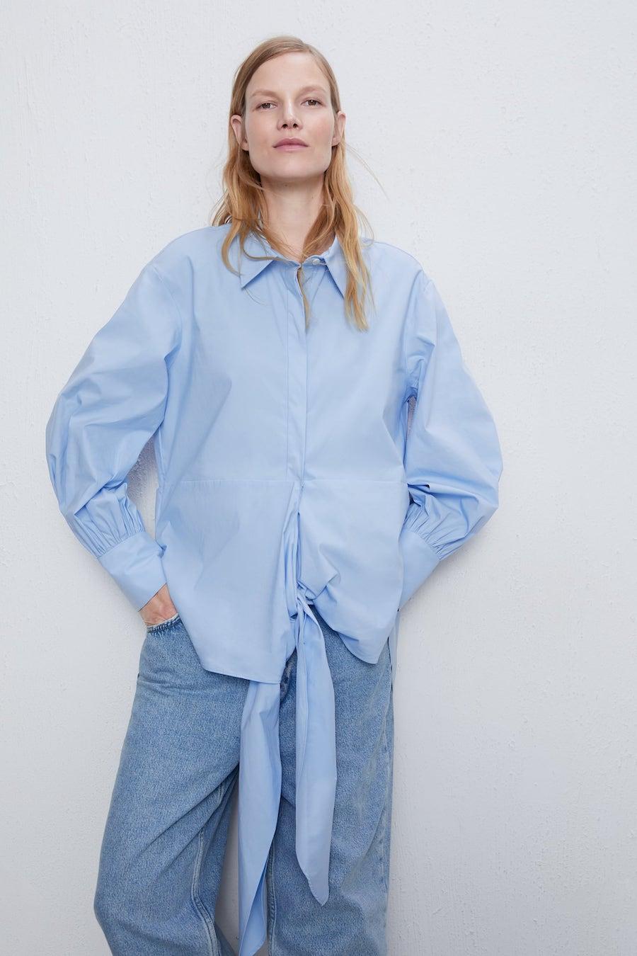 Camisa de cuello y solapa con manga larga acabada en puño con pliegues.