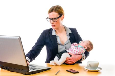 Mujer al ordenador con el niño en brazos