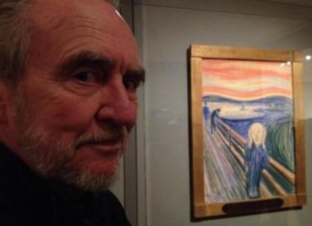 Wes Craven junto al cuadro que inspiró la máscara de Scream