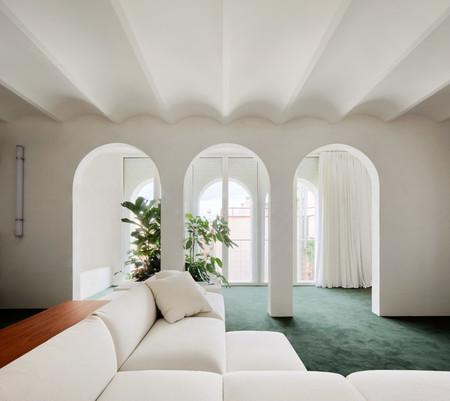 Este piso en Barcelona ha convertido el muro de carga que lo cruza en su elemento más singular, gracias a los arcos que lo abren permitiendo su circulación