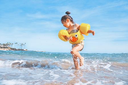 niña con manguitos jugando en la orilla