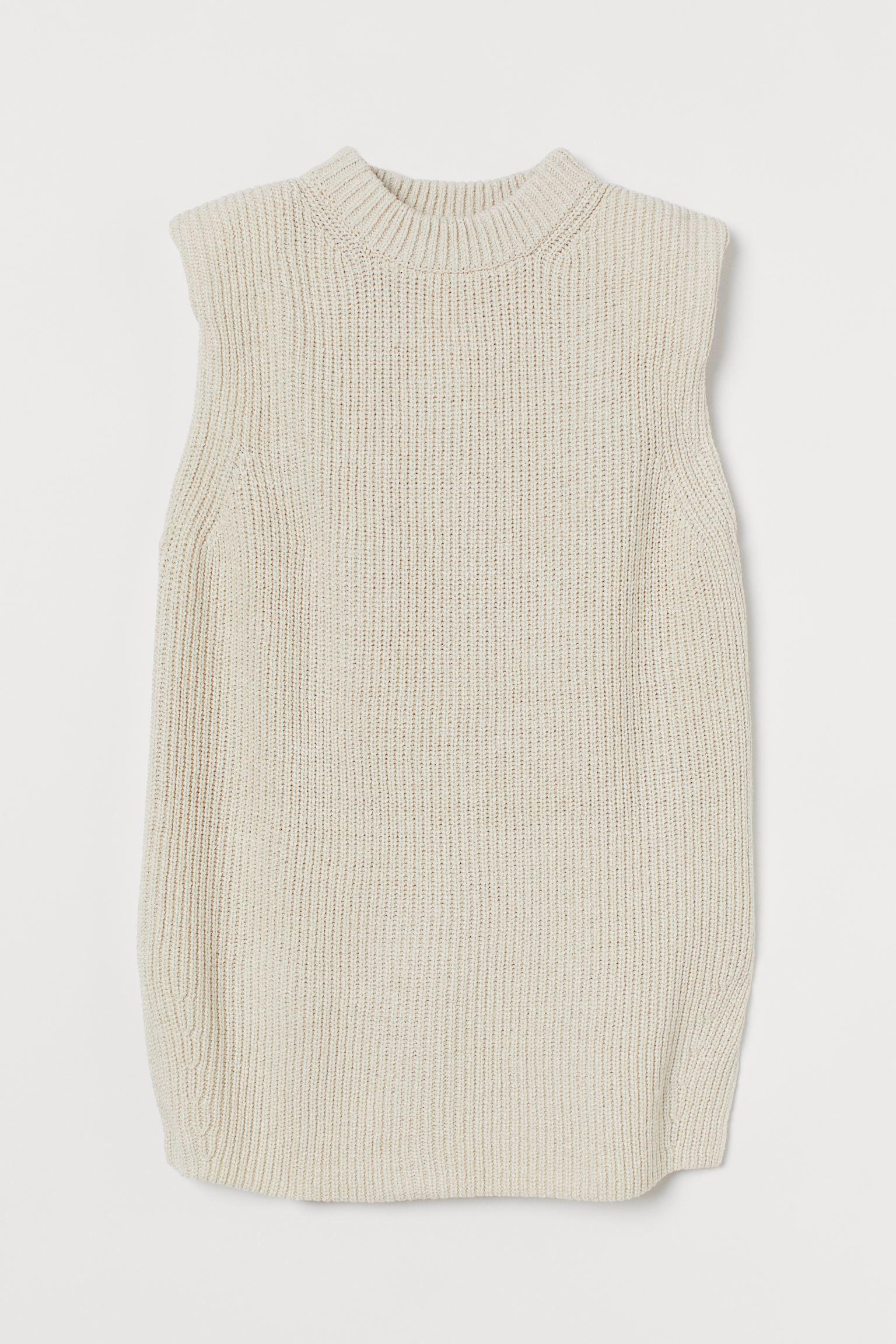 Suéter sin mangas en punto de canalé. Modelo oversize con hombreras, cuello de canalé y bajo recto con aberturas laterales inclinadas.