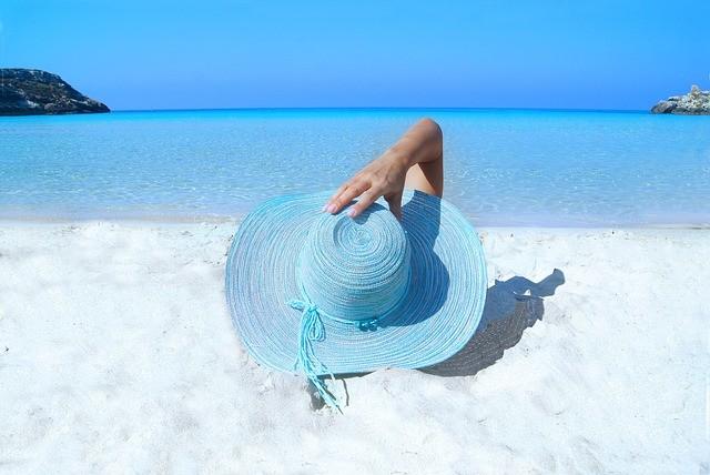 Mujer tumbada en la arena de la playa con pamela azul.