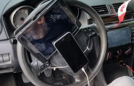 La gente está empezando a atar tablets y móviles al volante. Multar o educar, he ahí la cuestión