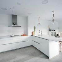 Puertas abiertas: una cocina discreta y blanca conectada con el salón-comedor