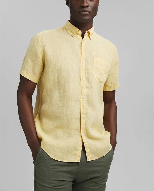 Camisa regular fit de color amarillo lisa. Tiene cuello clásico y un bolsillo en el pecho.