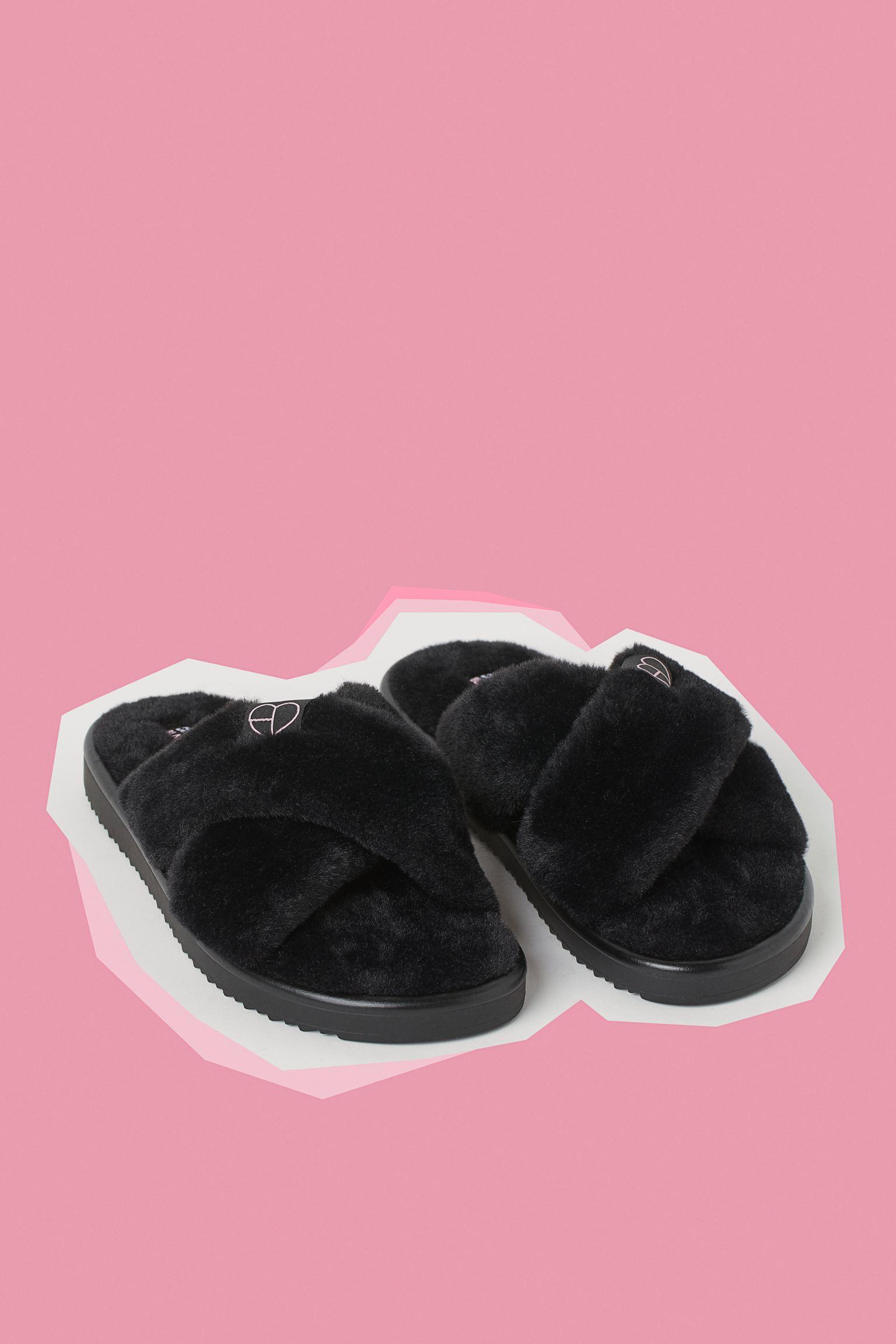 Zapatillas de casa con tiras cruzadas en pelo sintético suave y aplicación de tela arriba. Suela acanalada.