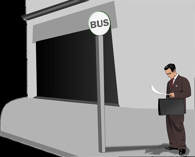 Parada de bus y hombre con traje leyendo.