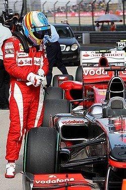 Fernando Alonso echando un vistazo al McLaren MP4-25 de Jenson Button en el parque cerrado