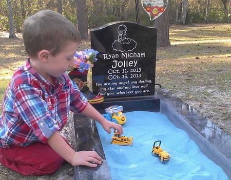 Una madre coloca un arenero en la tumba de su hijo para que su hermano mayor pueda jugar mientras le visita