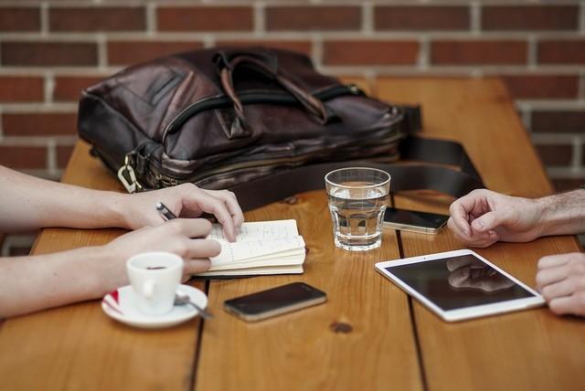 Dos personas en una mesa con libreta y tableta trabajando.