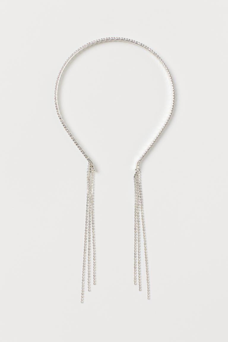 Diadema fina de metal con cadenas largas de strass que se prolongan por detrás de las orejas.