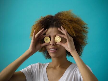 Mujer con dos monedas físicas emulando a Bitcoin ubicadas frente a sus ojos.