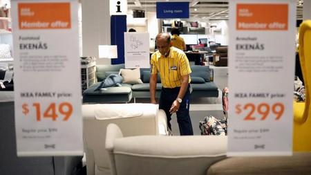Un trabajador en una tienda de Ikea se dispone a levantar un sofá.