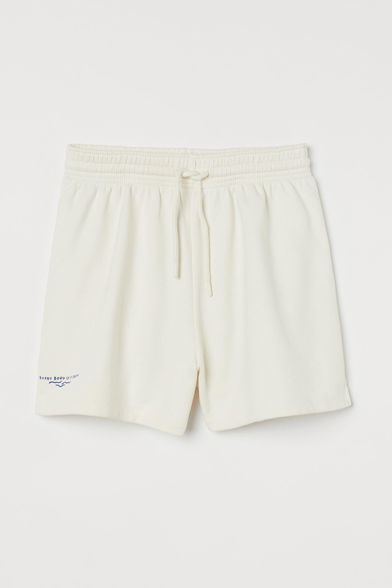 Pantalón corto en tejido sudadera suave de algodón con motivo de texto en una pernera. Modelo con cintura estándar elástica con cordón de ajuste, bolsillos al bies discretos y perneras rectas con aberturas laterales cortas.