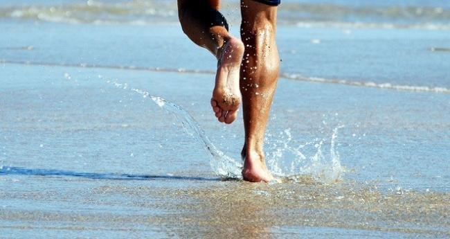 hombre corriendo en la orilla de la playa