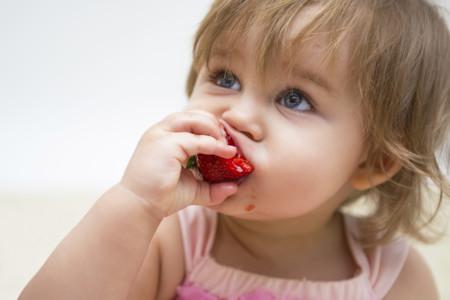 Nina Comiendo Fruto Rojo