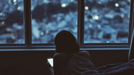 chica de noche en la cama mirando el móvil