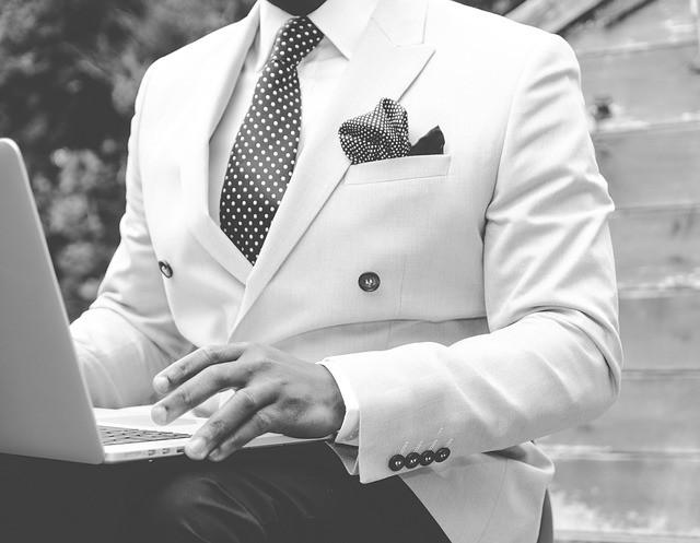 Hombre con traje, sentado en escaleras con un portátil.