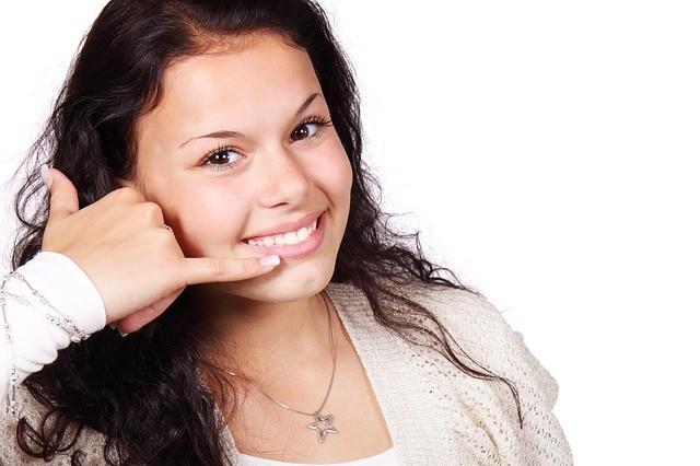 Chica joven realizando el gesto de llamar por teléfono.