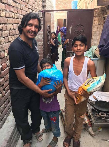 Muhammad Sultan repartiendo comida y ropa en Pakistán