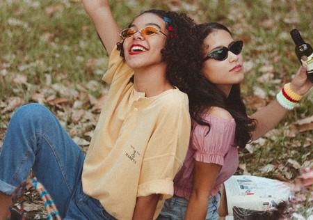 Two Smiling Women Holding Bottle Sitting On Green Grass 3491674