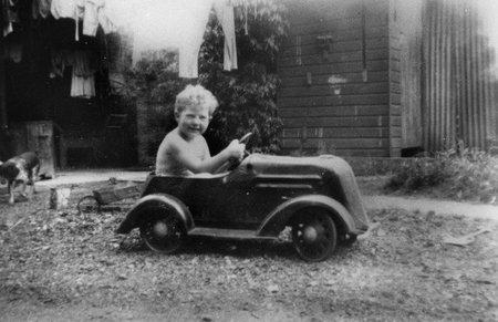 Niño jugando con un coche de pedales