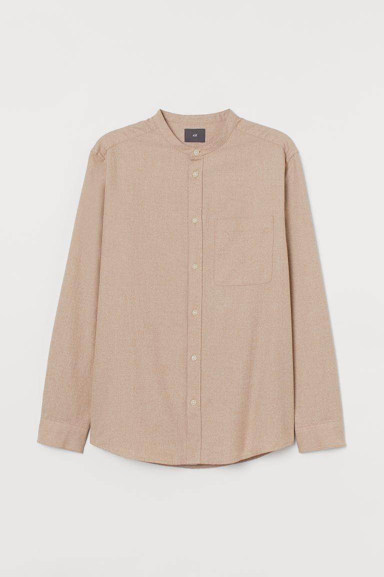 Camisa en tejido de algodón. Modelo con cuello mao, tapeta clásica, canesú detrás, un bolsillo superior abierto, mangas largas con botón en los puños y bajo redondeado.