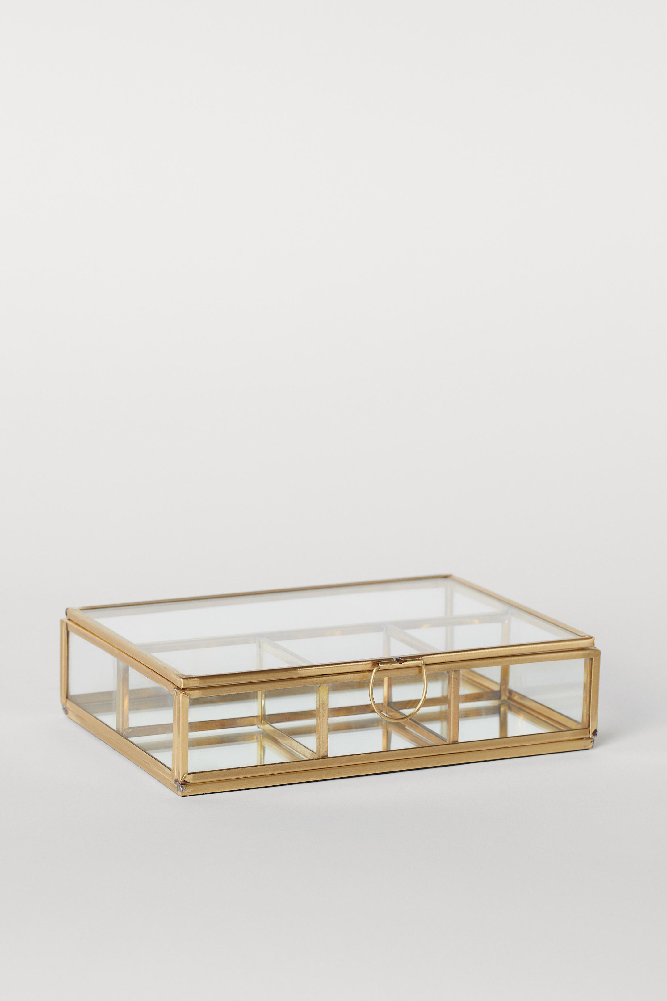 Joyero rectangular en vidrio transparente con marco de metal y base de espejo. Tapa con anilla pequeña delante y cuatro compartimentos en el interior. Base acolchada. Medidas 4,5x12,5x17,5cm.