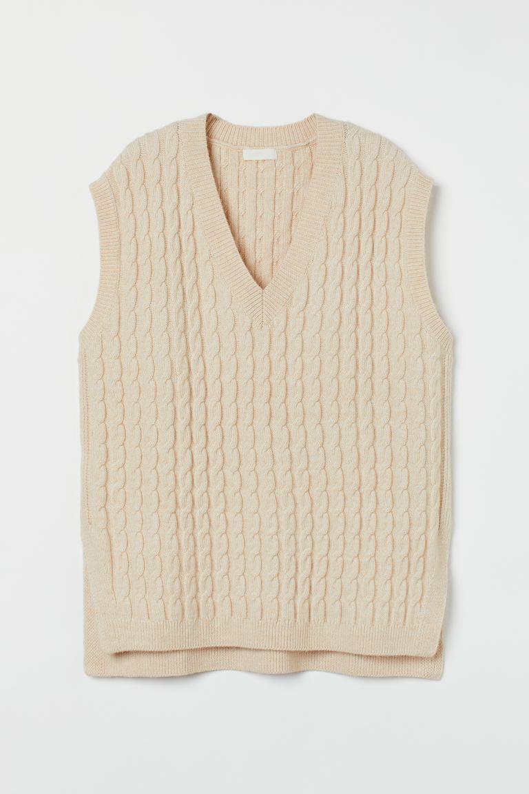 Suéter sin mangas en punto trenzado suave con lana en la trama. Modelo de corte relajado con escote de pico, hombros ligeramente caídos con sisas amplias y bajo recto con aberturas laterales en ángulo.