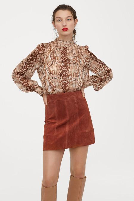 Falda corta de ante con costuras decorativas. Modelo de talle alto con cremallera visible y botón oculto detrás.