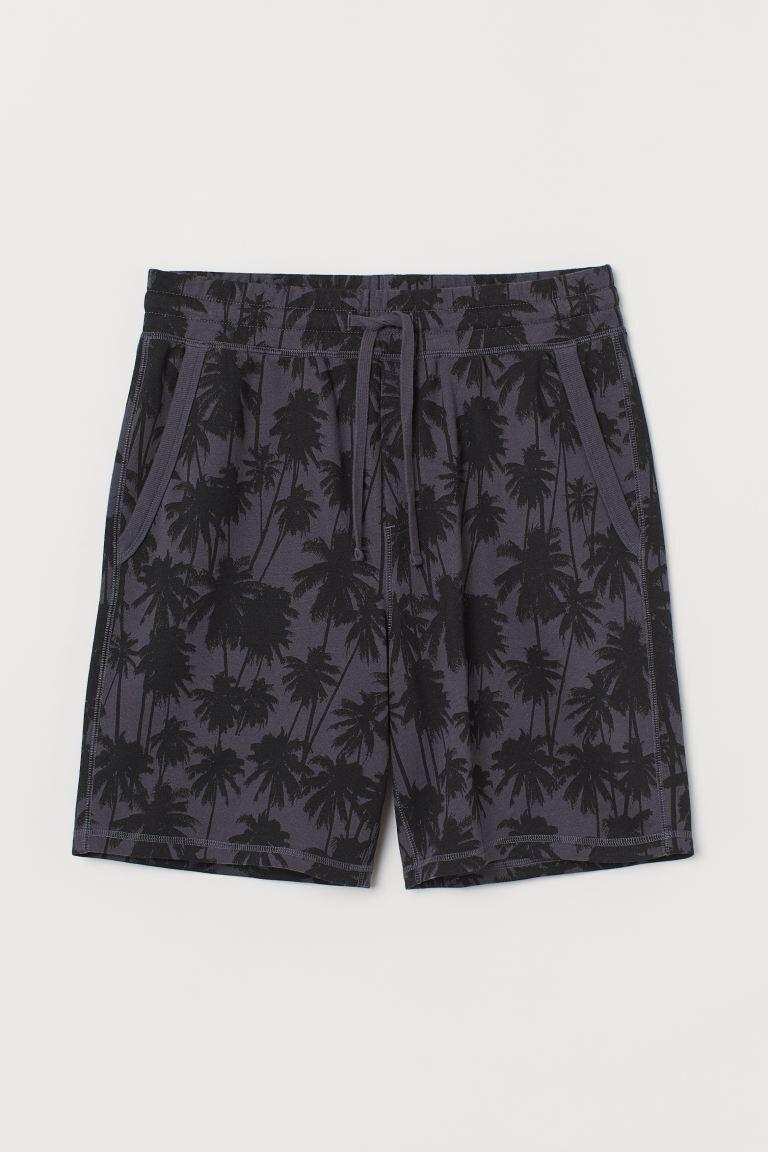 Pantalón corto con estampado de palmeras en sudadera