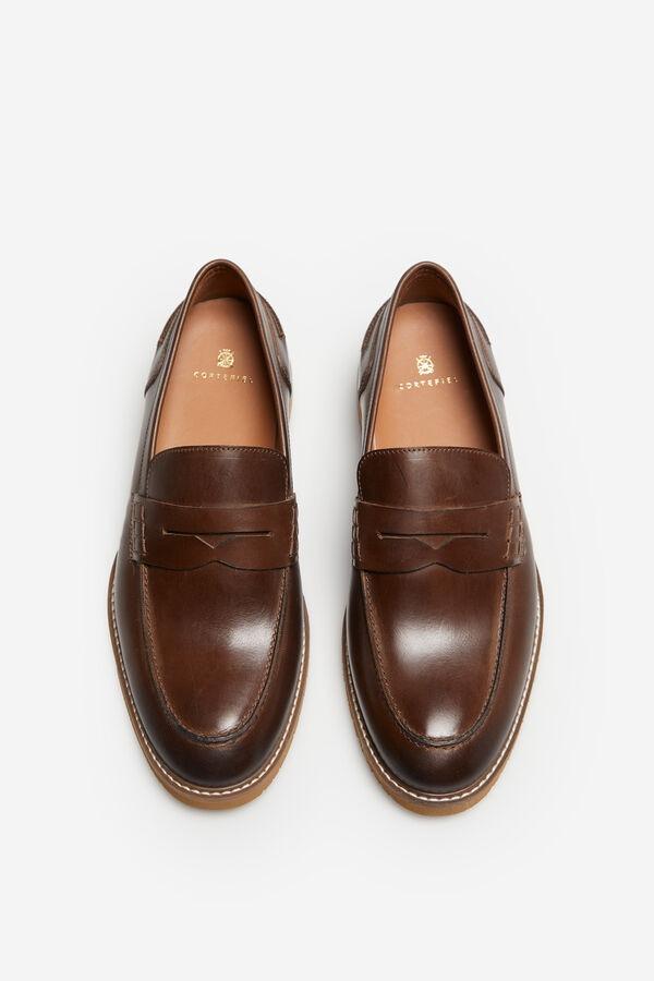 Zapato mocasín con antifaz en piel lisa. Esta hecho en una construccion con suela de goma ultraflexible y con una plantilla extraible para darle la maxima comodidad.