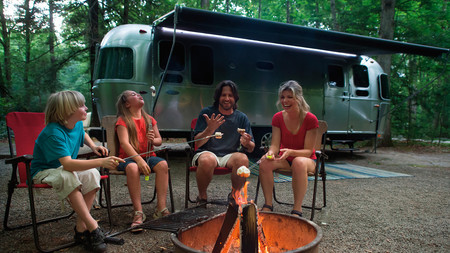 Family Traveling Together By Fire Pit Airstream Flying Cloud