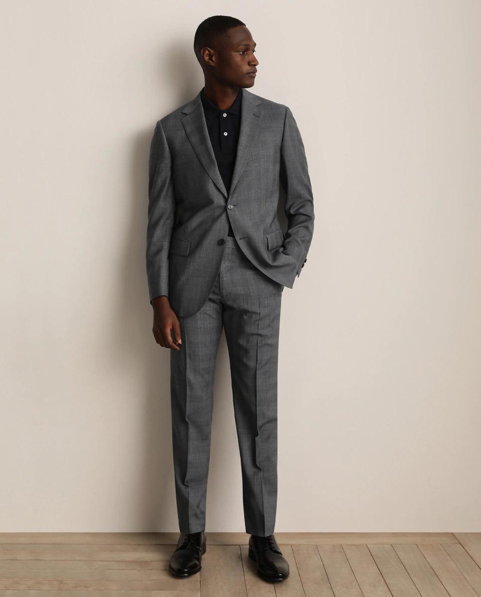 Traje modelo Oxford príncipe de gales color azul grisáceo. La americana con forro y cierre de dos botones, tiene las solapas de muesca y tres bolsillos delanteros. El pantalón sin pliegues, tiene un cierre asimétrico de botón y cremallera.