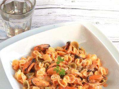 Margaritas de pasta con mejillones en salsa de tomate y nata. Receta italiana