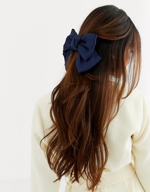 Pasador para el pelo con lazo extragrande de satén en azul marino.