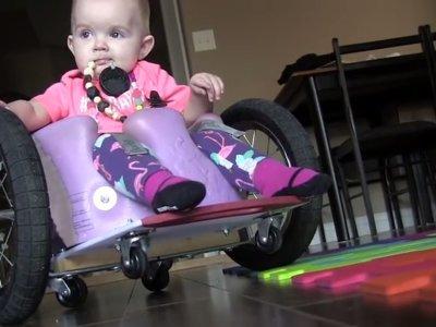 Fabricaron una silla de ruedas casera para su hija de 13 meses con parálisis (y la domina así de bien)