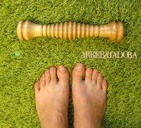Automasaje en los pies con el rodillo de madera tras un día con tacones