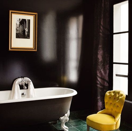 Un baño negro con bañera exenta.