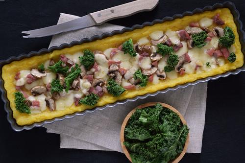 Tarta salada de polenta con champiñones, col kale, jamón y queso: receta original (y sin gluten) para salir de la rutina