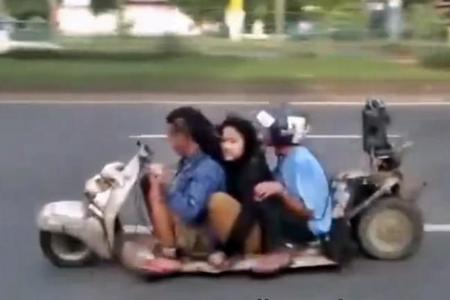 Tres cabezabuques filipinos haciendo el <em>caganer</em> en una Vespa <em>lowrider</em>