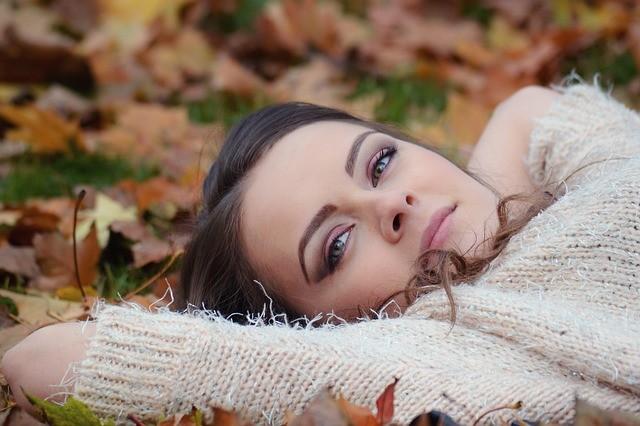 Chica tumbada sobre hojas en un parque en otoño.