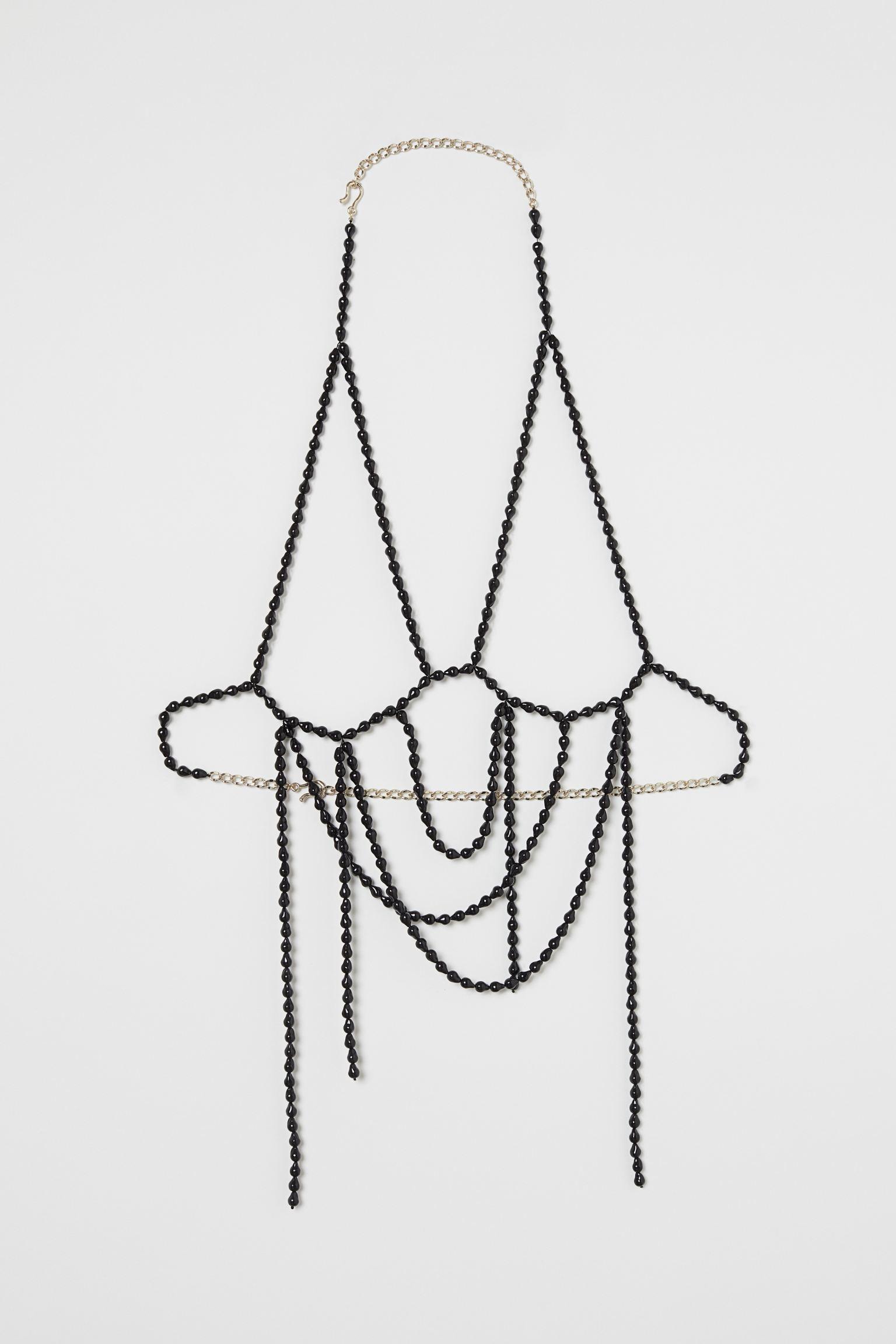 Studio Collection. Cadena corporal de perlas de acrílico reciclado con cadena de metal parcialmente reciclado. Copas preformadas y cierre en nuca y cintura.