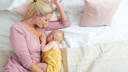 Mamá dando de mamar a su bebé en posicion Acostada De lado