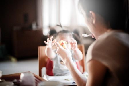 Madre dando de comer a su bebé con cuchara